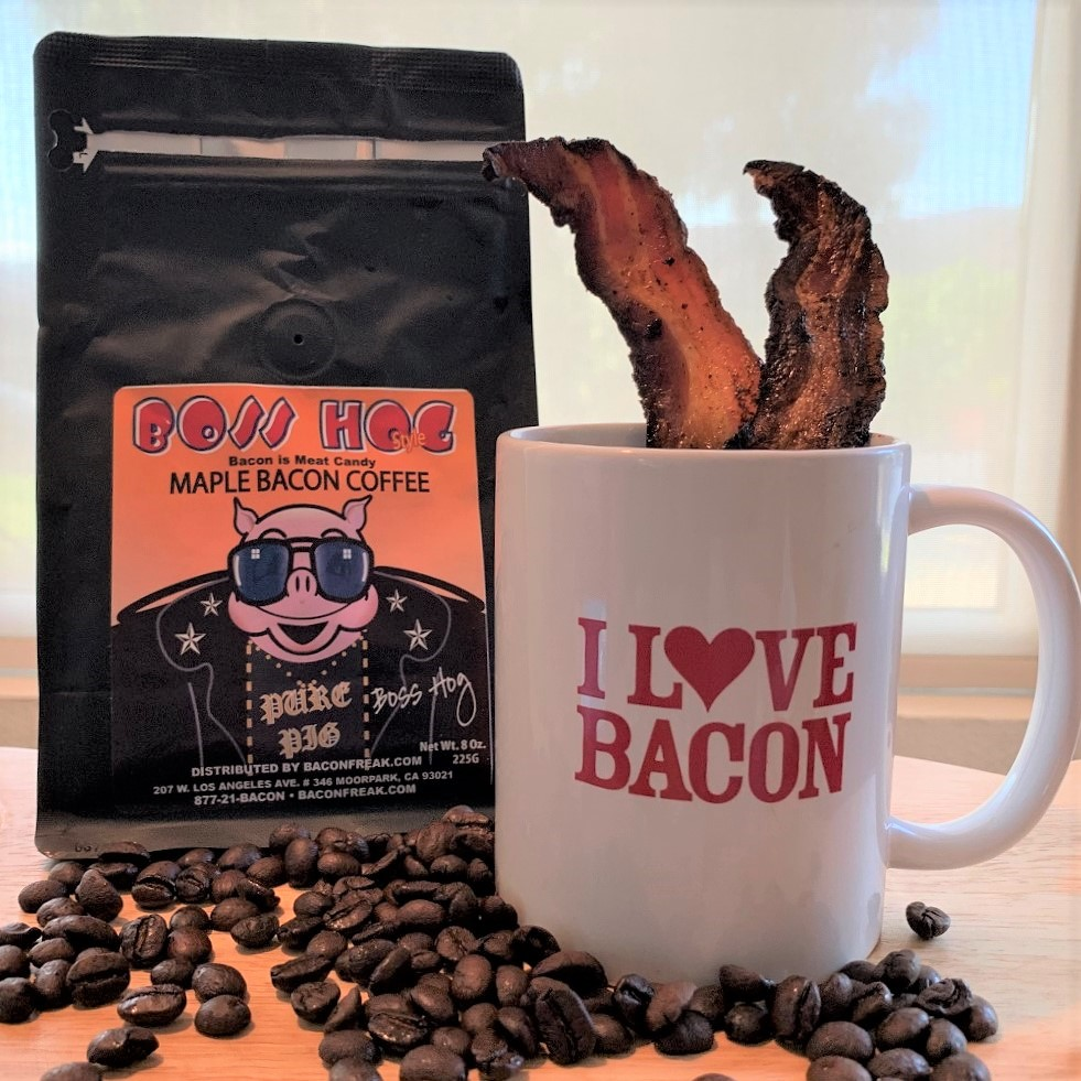 Bag of Boss Hog maple bacon coffee beans and a I Love Bacon Mug with two strips of cooked bacon as swizzle sticks.